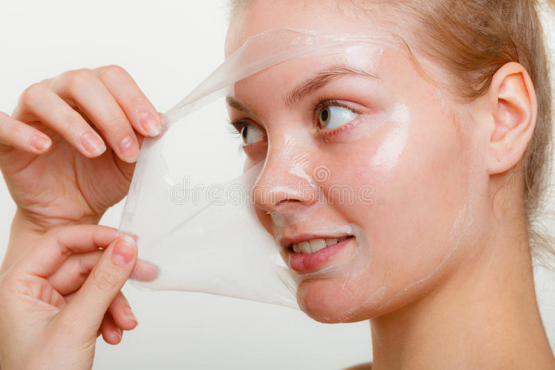 Woman removing facial peel off mask. royalty free stock images