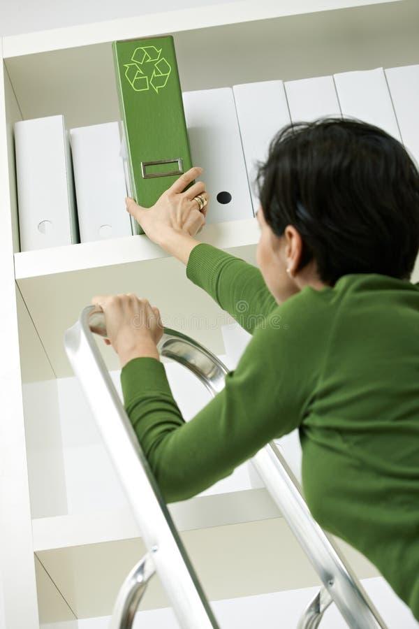 Woman removing green folder from shelf. Office worker on ladder removing green folder with recycling symbol from shelf stock image