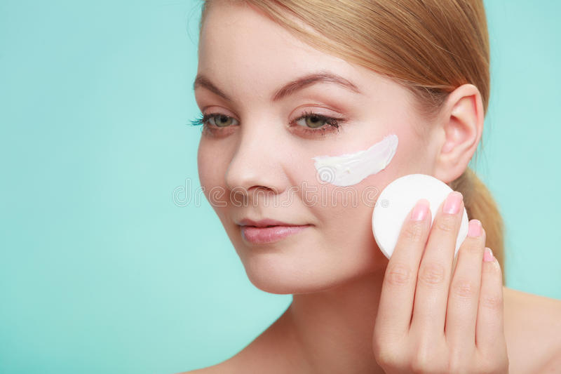 Woman removing makeup with cream and cotton pad royalty free stock photography