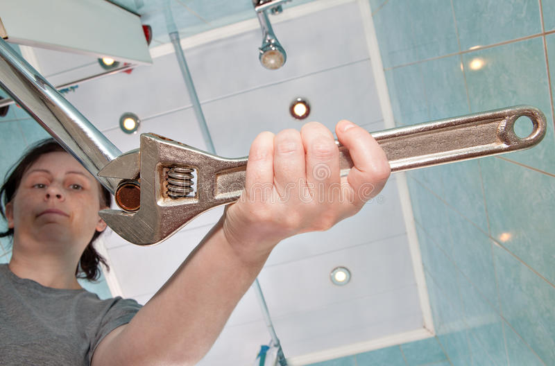 Woman removing old tap aerator using an adjustable plumbing span. Woman unscrews the old, wrong faucet aerator to sink in the bathroom, using an adjustable stock photos