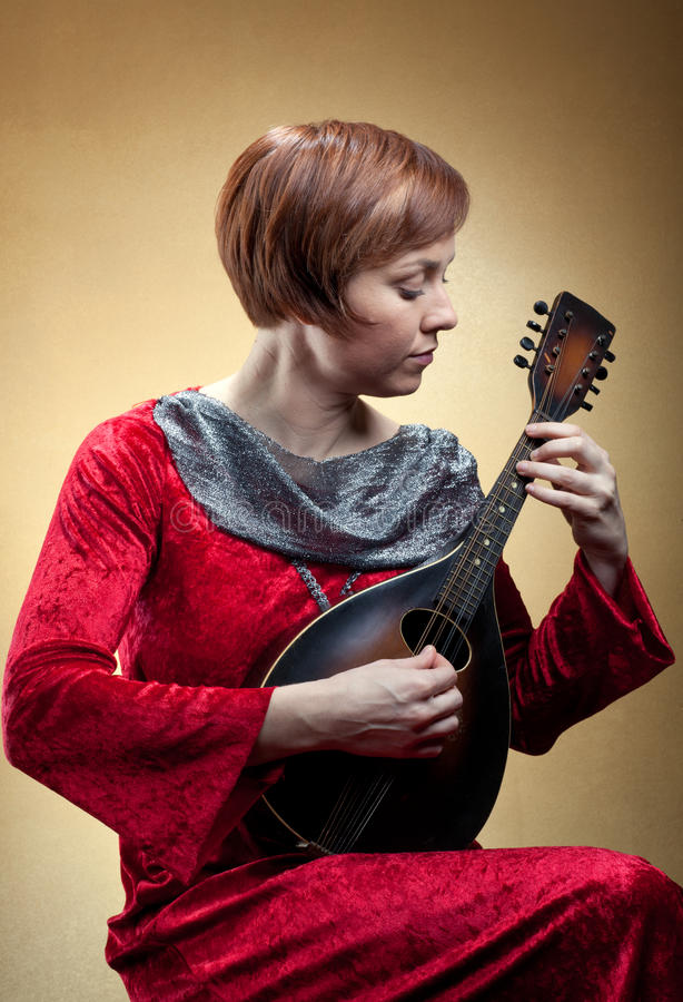 Woman in renaissance costume playing mandolin royalty free stock photo