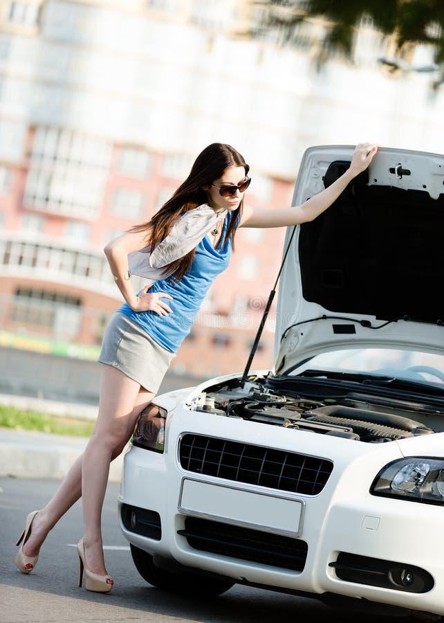 Woman repairing the broken car on the road stock image