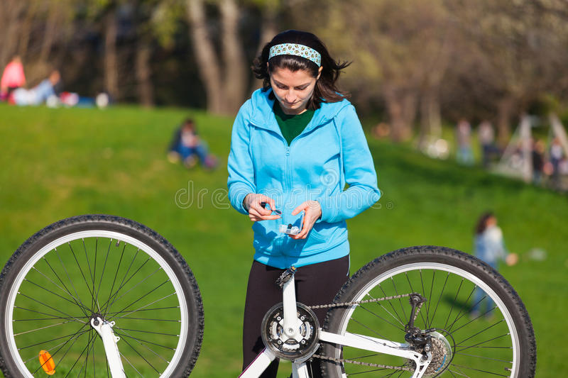 Woman repairing flat tire. Young woman is repairing the flat tire of her bike royalty free stock image