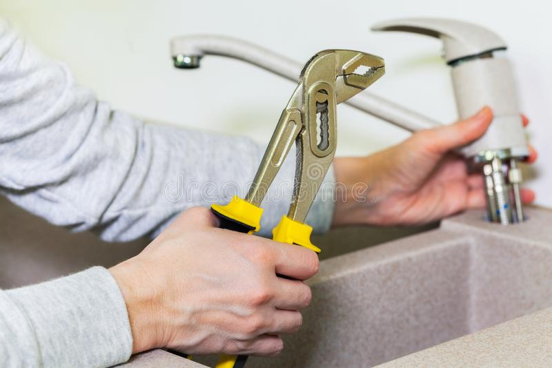 Woman repairing kitchen tap royalty free stock photography