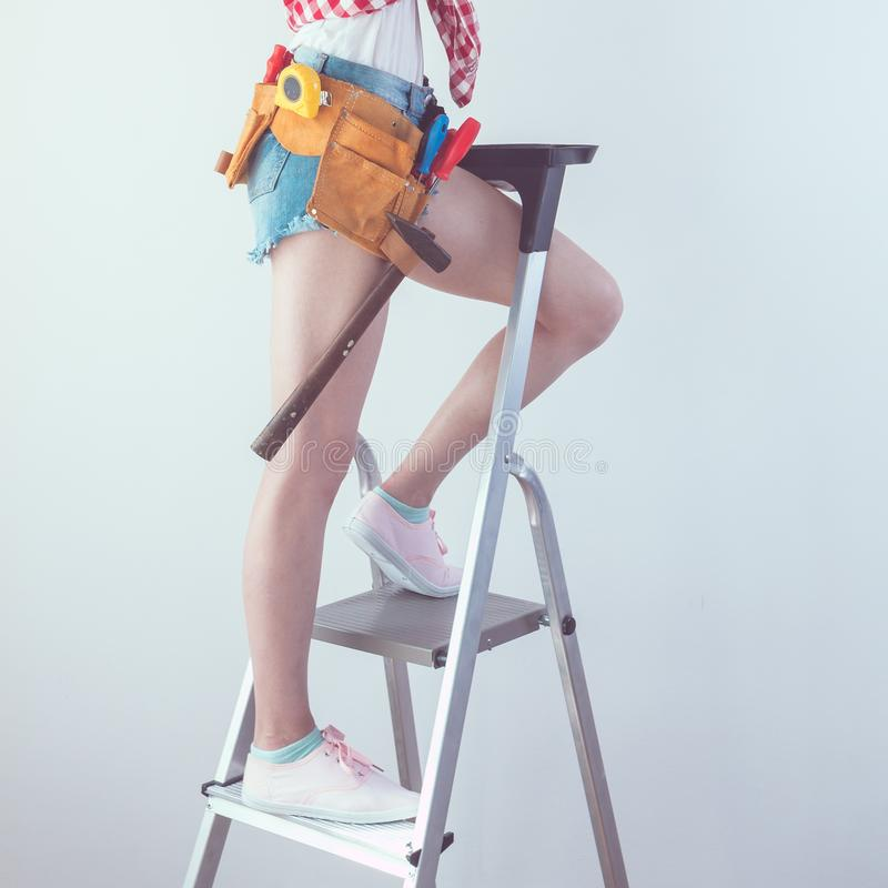 Woman with repairing tools and ladder stock image