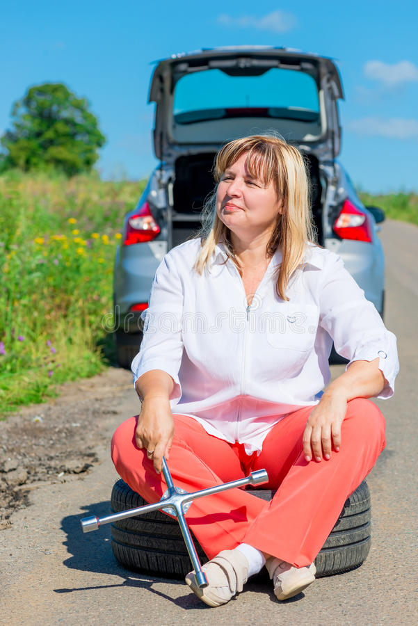 Woman after replacing the bursting of the wheel rests royalty free stock images