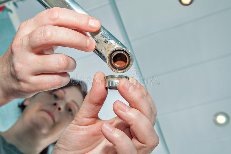 Woman replacing old wrong aerator for tap, hands handyman close-up. Woman replaces the old clogged aerator for faucet in the bathroom, hands handyman closeup royalty free stock photo