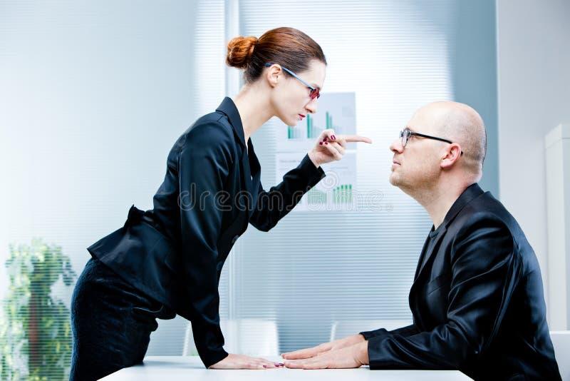 Woman reproaching man at work stock photos