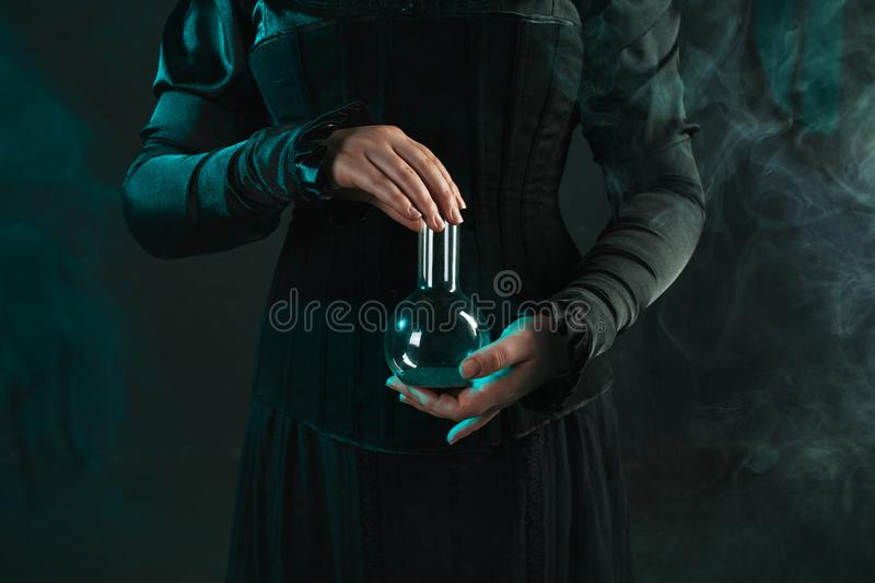 Woman is a research scientist holding a flask with the material. Concept of scientific research and history of science. stock image