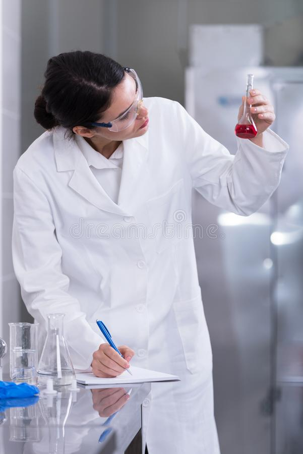 Woman researcher doing a lab test and making notes stock photo