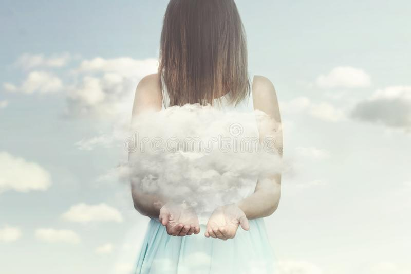 Woman resembling an angel guards a small cloud in her hands royalty free stock photo