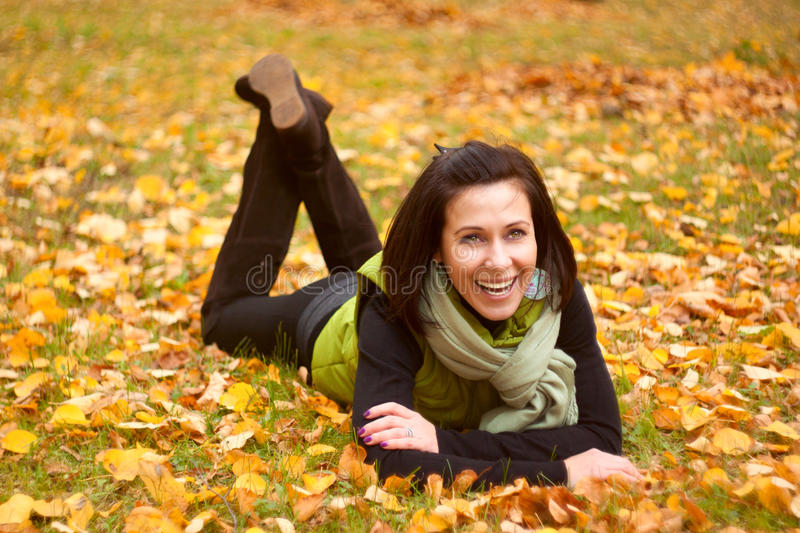 Woman rest in the autumn park. Young pretty woman rest in the autumn park royalty free stock image