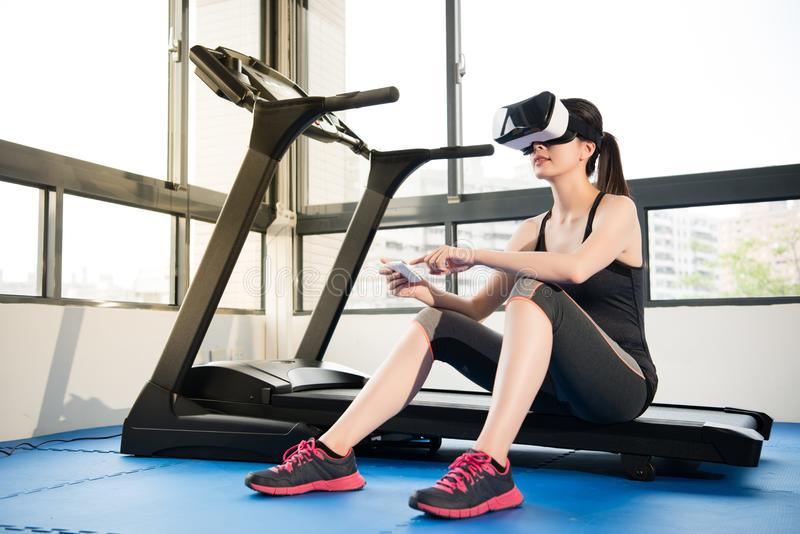 Woman rest treadmill with VR headset control by smartphone. Beauty asian woman rest on treadmill with virtual reality control by smartphone. VR headset glasses stock photo