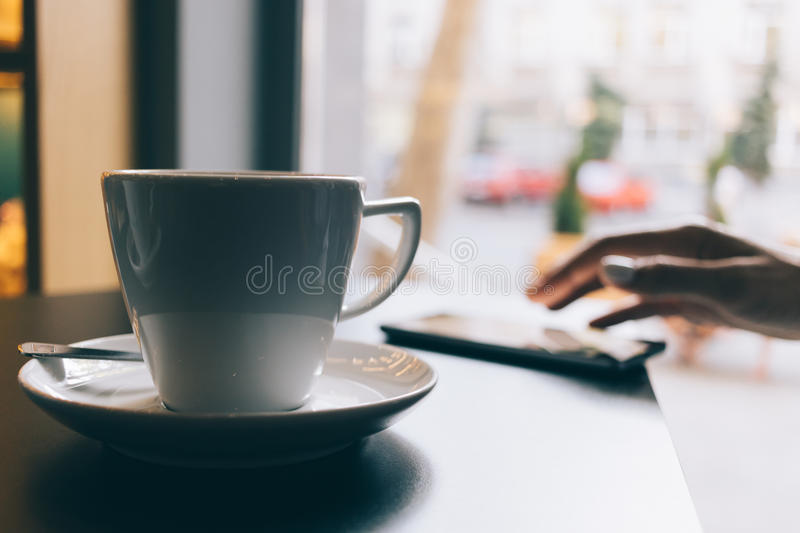 Woman in a restaurant drinking coffee and using a mobile phone stock photo