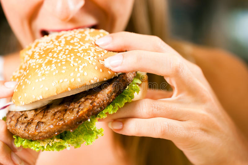 Woman in a restaurant eating hamburger. Happy woman in a restaurant eating a fast food hamburger, focus on the burger stock photos