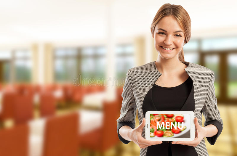 Woman restaurant manager holding tablet with menu royalty free stock images