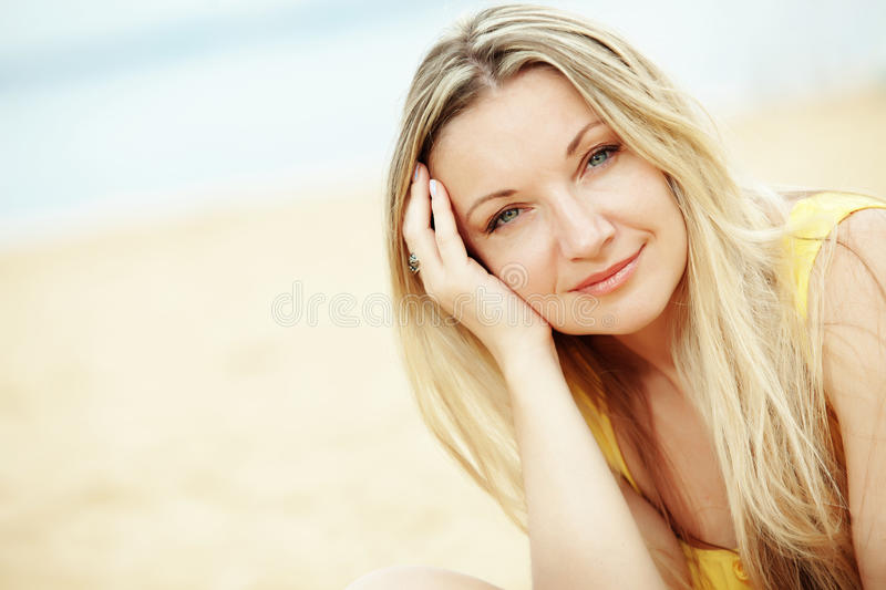 Woman resting at the beach. Middle aged woman resting at beach near the sea royalty free stock images