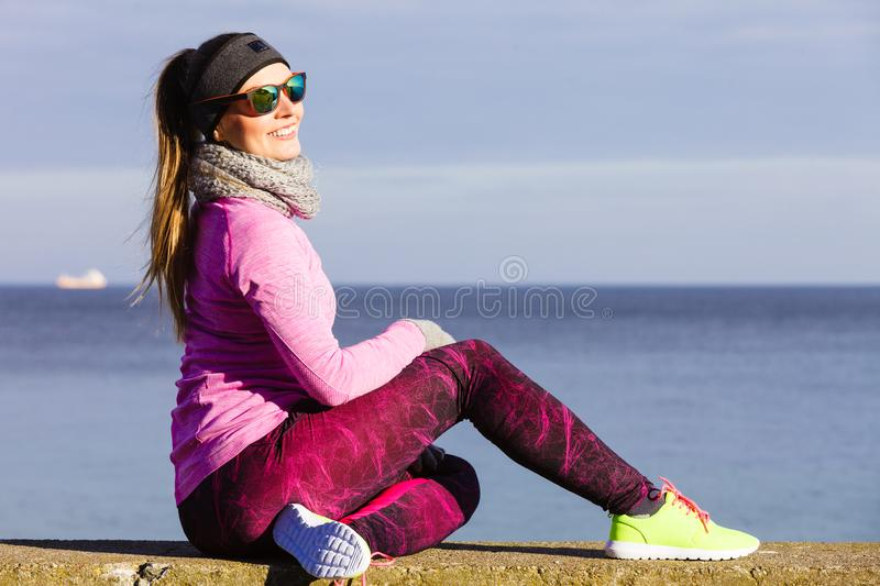Woman resting after doing sports outdoors on cold day stock photo