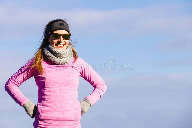 Woman resting after doing sports outdoors on cold day. Woman resting relaxing after doing sports outdoors. Fitness girl female jogger wearing warm sporty clothes royalty free stock images