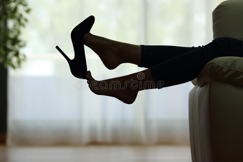 Woman resting with feet taking off shoes. Back light silhouette of a woman resting with feet taking off shoes on a couch at home with a window in the background stock photography