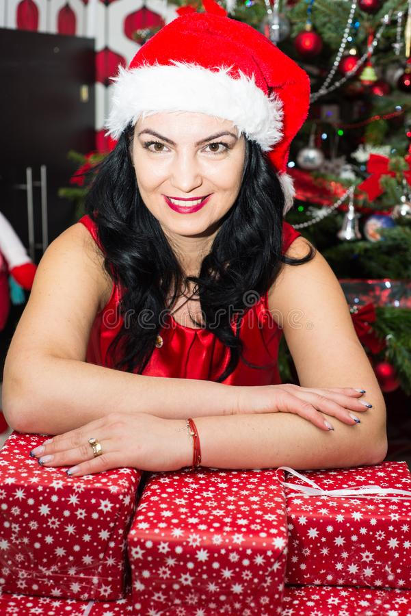 Woman resting hands on Xmas gifts. Smiling woman with santa hat resting hands on many Christmas gifts royalty free stock photo