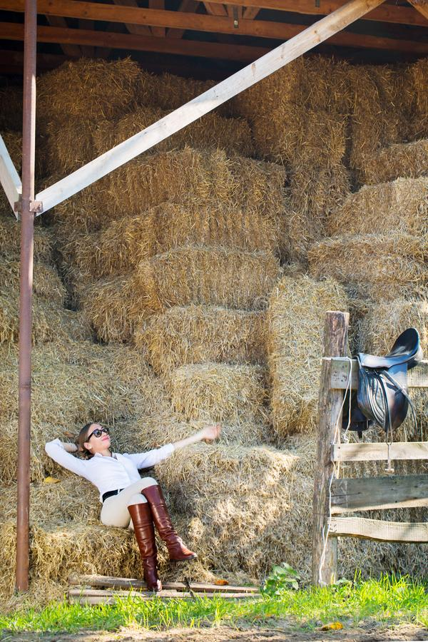 Woman resting in the hayloft. A beautiful woman in a horse riding costume resting in the hayloft stock photography