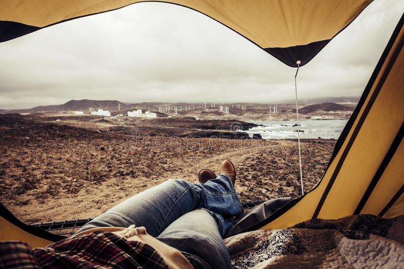 Woman resting inside a tent with beautiful landscape outdoor - travel amd wanderlust alternative lifestyle concept for people love. Freedom and nature - explore royalty free stock images