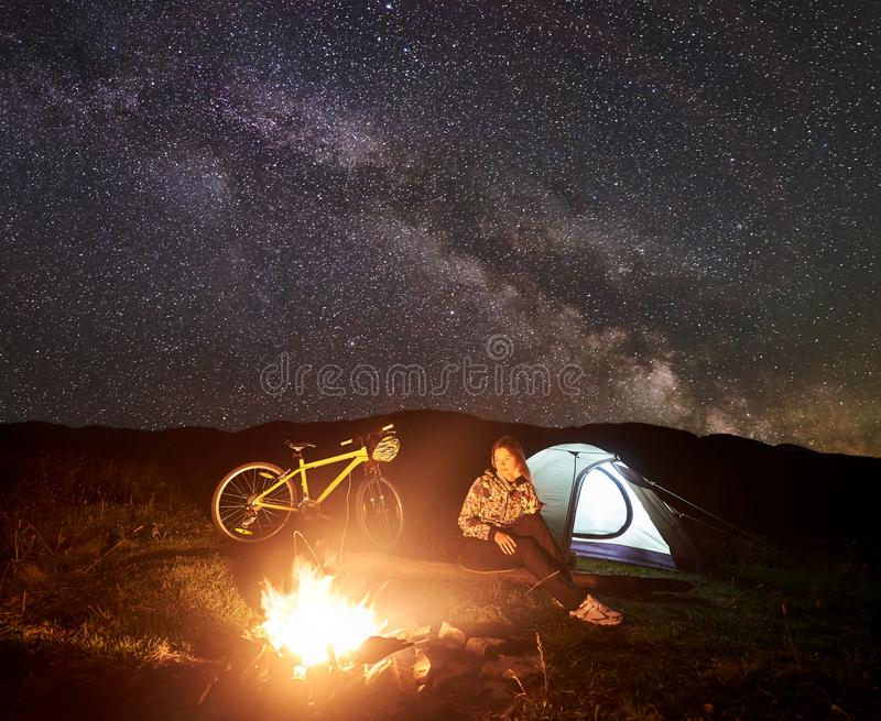 Woman resting at night camping near campfire, tourist tent, bicycle under evening sky full of stars. Young woman cyclist resting at night camping near burning royalty free stock images