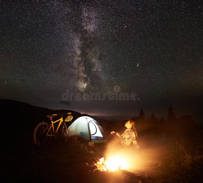 Woman resting at night camping near campfire, tourist tent, bicycle under evening sky full of stars. Young woman tourist enjoying at night camping near burning royalty free stock image