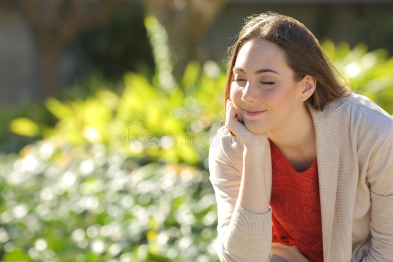Woman resting relaxing in a park a sunny day. Satisfied woman resting relaxing sitting in a park a sunny day royalty free stock images