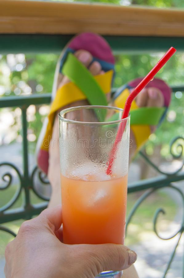 Woman resting sitting on the balcony with openwork metal bars, holding a misted glass with a cold summer drink and a straw, female stock photo