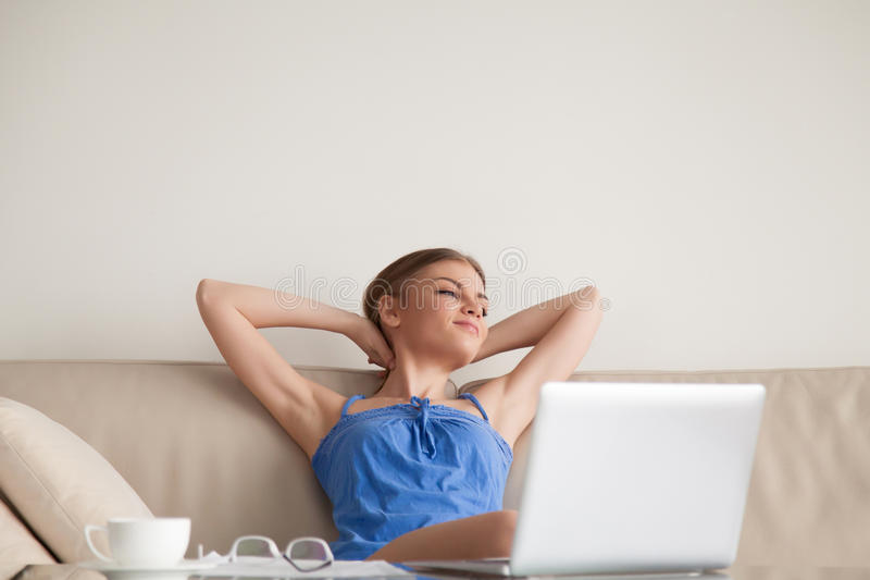 Woman resting on sofa at home after work done. Satisfied young woman sitting on comfortable soft sofa at home with hands behind head in front of laptop, resting stock photography
