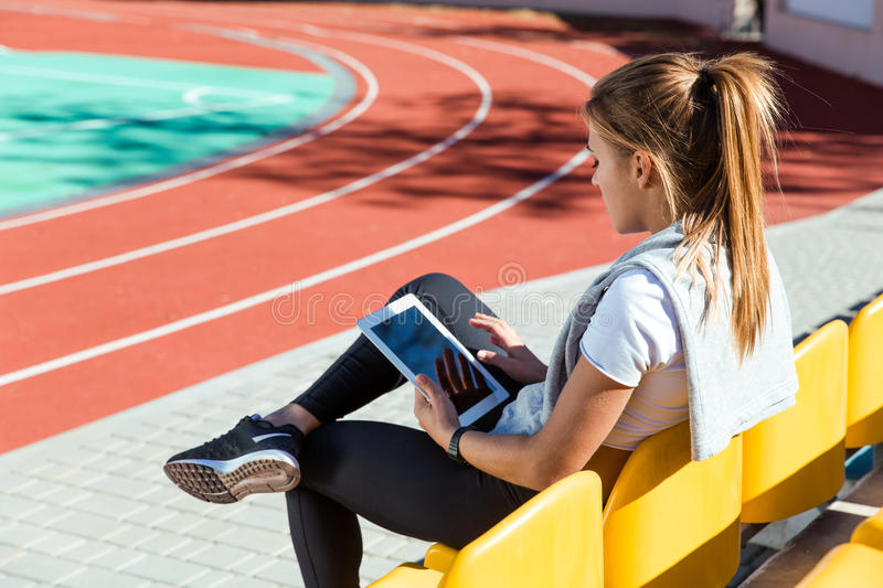Woman resting with tablet computer at stadium royalty free stock images