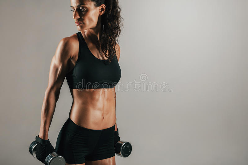 Woman resting weights at her sides while looking. Three quarter view on gorgeous single athletic woman resting with chrome finished dumbbell weights at her sides stock photos