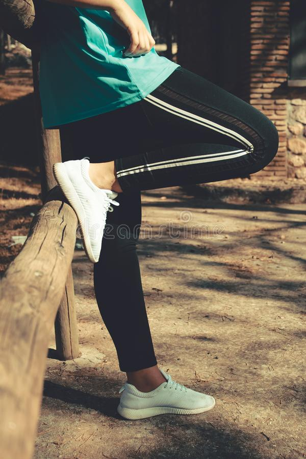 A woman resting in a wooden fence wearing sport clothes stock photos