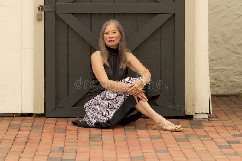 Woman rests by locked door stock photography
