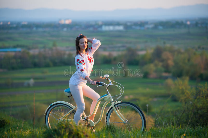 Woman with retro bike on the hill in the evening. Beautiful female sitting astride on bicycle in Ukrainian embroidery at hill and looks into the camera on a stock image