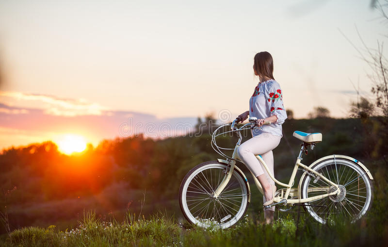 Woman with retro bike on the hill in the evening. Beautiful sunset and girl in Ukrainian embroidery with retro bike enjoying them. Blurred background stock photo
