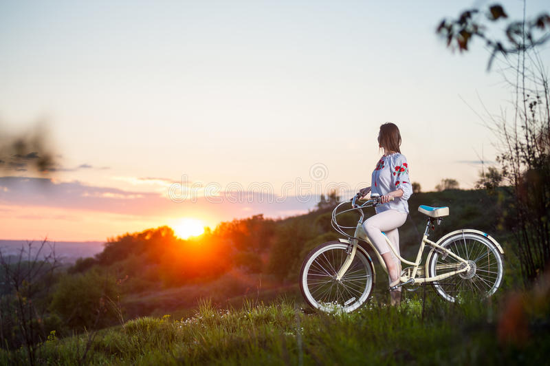 Woman with retro bike on the hill in the evening. Beautiful sunset and sporty woman with bicycle enjoying them. Blurred background stock photo