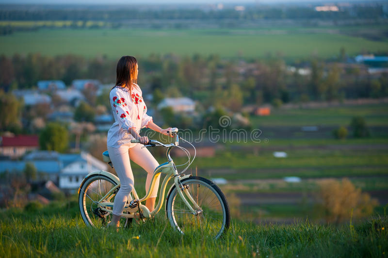 Woman with retro bike on the hill in the evening. Brunette female sitting astride on bicycle in Ukrainian embroidery at hill and looks into the distance on a stock image