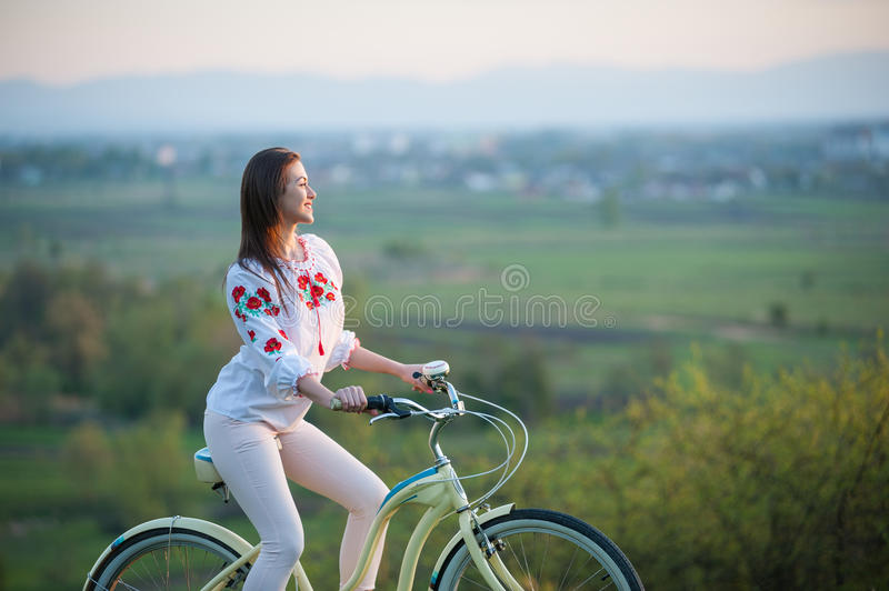 Woman with retro bike on the hill in the evening. Smiling brunette female sitting astride an bicycle in Ukrainian embroidery at hill and looks into the distance royalty free stock image