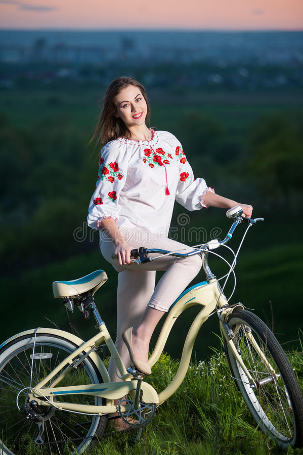 Woman with retro bike on the hill in the evening. Smiling female in Ukrainian embroidery holding vintage bicycle at hill on a blurred background of greenery and royalty free stock images