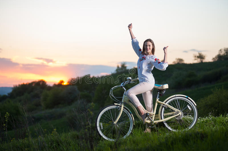 Woman with retro bike on the hill in the evening. Smiling woman in Ukrainian embroidery with retro bike standing at hill and showing thumb up gesture of good stock image