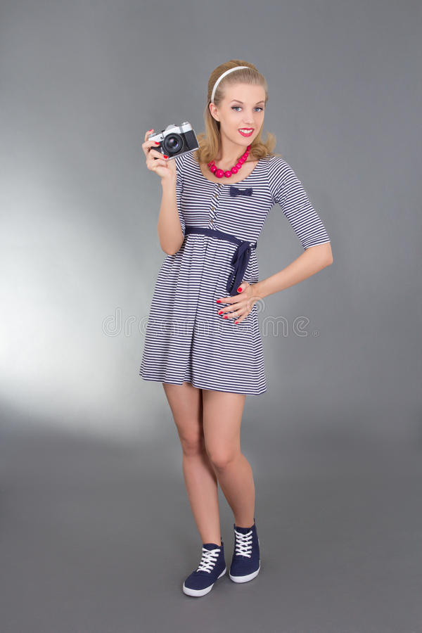 Woman in retro clothes posing with photo camera stock photo