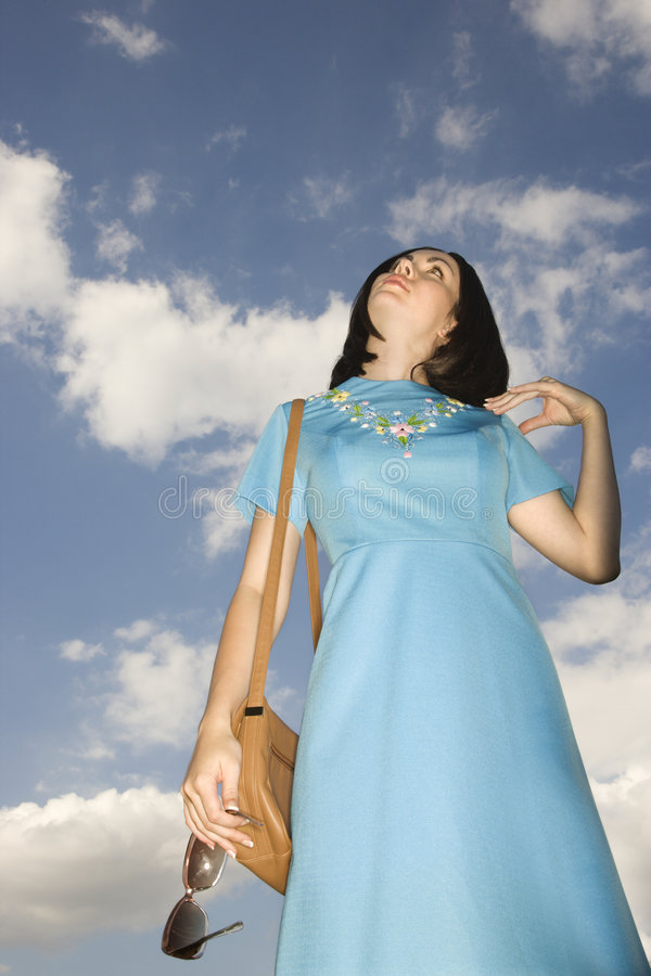 Woman in retro clothing. Caucasian young adult woman in retro clothing looking up at sky stock photos