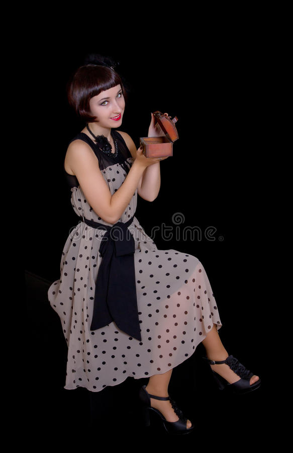 Woman in retro styled dress opening jewelry box royalty free stock photo