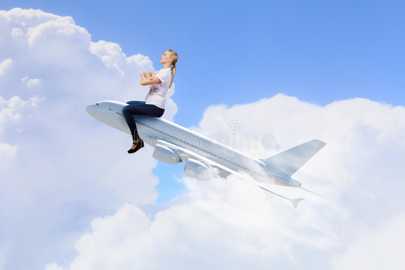 Woman ride airplane. Young woman riding drawn airplane flying in air stock photo