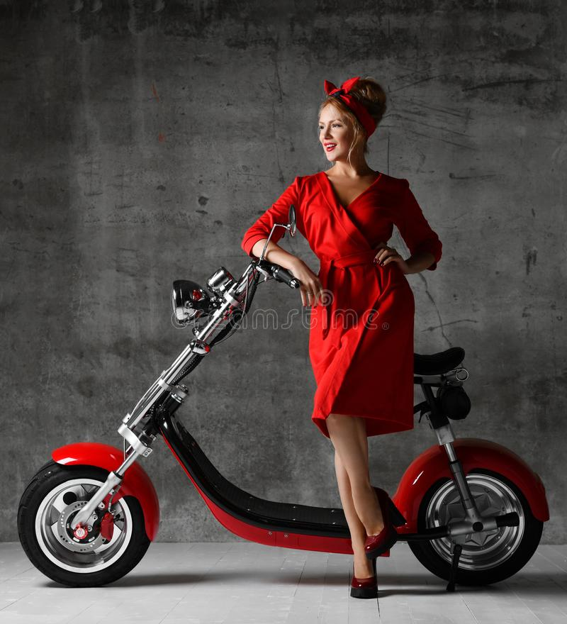 Woman ride sit on motorcycle bicycle scooter pinup retro style laughing smiling red dress royalty free stock photo