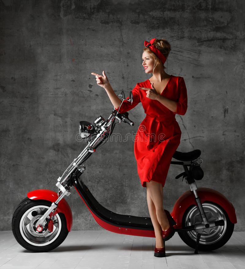 Woman ride sit on motorcycle bicycle scooter pinup retro style pointing fingers laughing smiling red dress royalty free stock photography