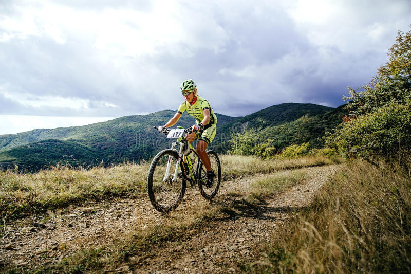 Woman rider cyclist riding uphill on a background of mountains and clouds stock photos